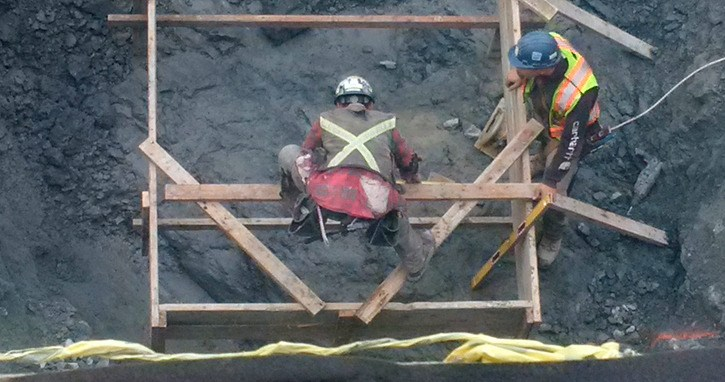 Construction workers in underground portion of commercial-residential building