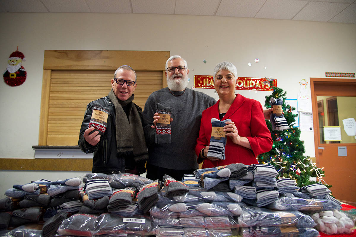 Rabbi Harry Brechner (left) Michael Bloomfield, founder of the Sock Project, and BC Finance Minister Carole James hold up some of the socks donated to 25 distribution centres in Greater Victoria. (Nicole Crescenzi/News Staff)